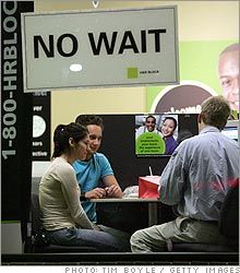 A tax preparer assists customers in an H&R Block office in Des Plaines, Illinois.